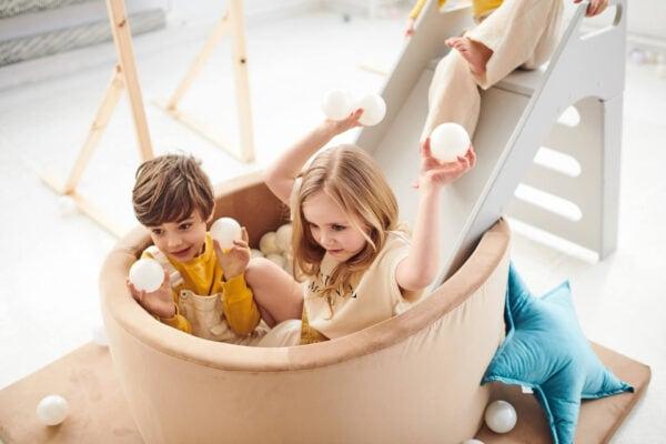 Dzieci rzucające piłeczkami w basenie