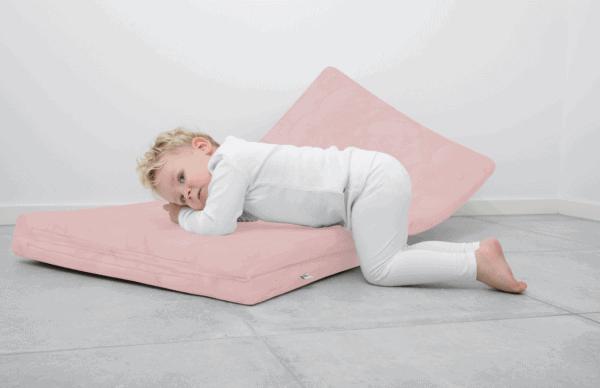 Dziecko leżące na różowej macie